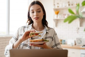 Beautiful focused woman working with laptop while eating sandwich